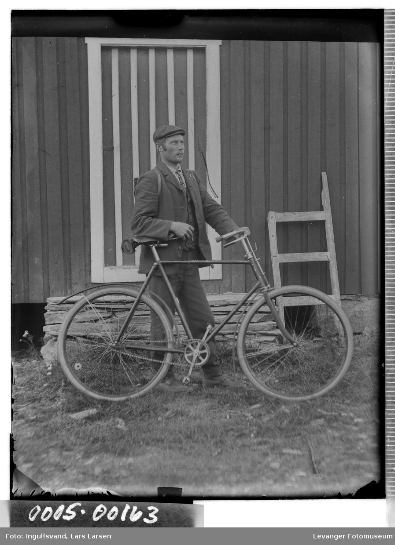 Portrett av mann med sykkel foran en trapp med en sladd i bakgrunnenen.