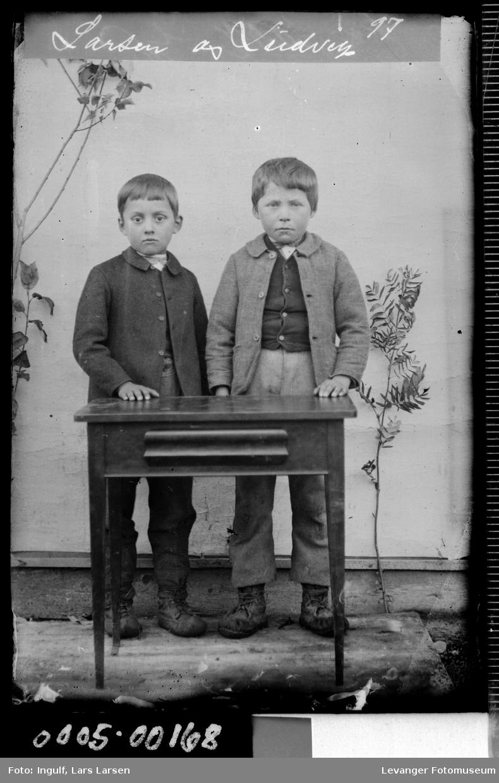 Portrett av to gutter ved et bord i helfigur.