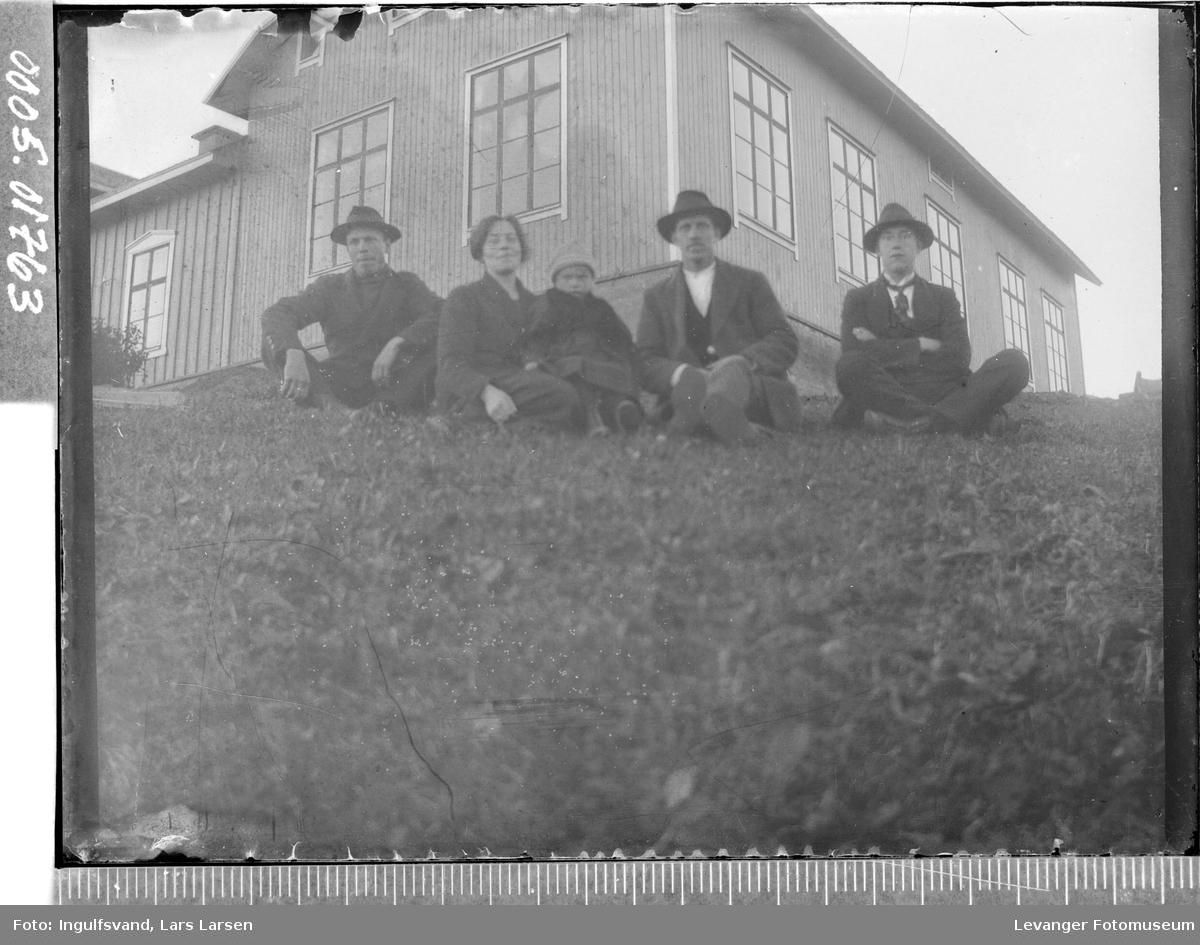 Gruppebilde av tre menn, en kvinne og et barn foran en bygning.