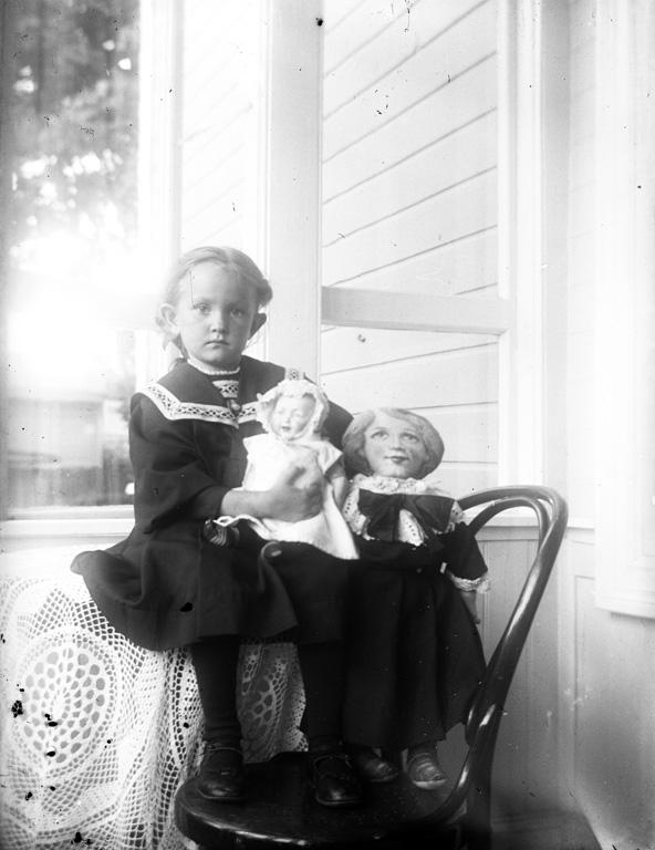 """Text till bilden:""""Flicka med docka, på stol""""."""