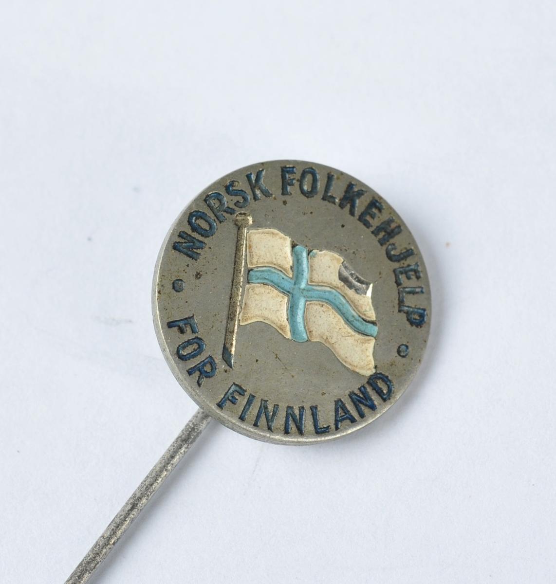 Sirkelforma, med tekst rundt ytterkanten og med det finske flagget i midten.