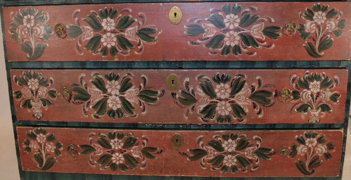 """Øverste skuffe har navnet """"Aagot Olsdatter Brager"""" og året """"1856"""" skrevet i sandfarvet løkkeskrift. Under denne står fødselsdatoen hennes skrevet i samme stil. På hver side av dette er der malt en blomsterbukett med blader på hver side, rosemaling i Valdres-stil.  Denne blomsterbuketten på hver side går også igjen i ytterkanten av de tre andre skuffene, men disse har i tillegg også et gjennomgående motiv malt mellom låsbeslaget i skuffenst midte og håntakaet. To hvite blomster med kronblader står over hverandre. Ut fra disse på hver side stikker en blomst i tulipanform, og mellom de fire blomstene står grønne blader i """"S"""" form. Videre rundt disse er der konvekse buer i sort og hvitt. Det finnes to av disse motivene på hver skuff.  Selve kisten er malt i en teknikk som gir loddrette striper i ulike blåsjatteringer."""