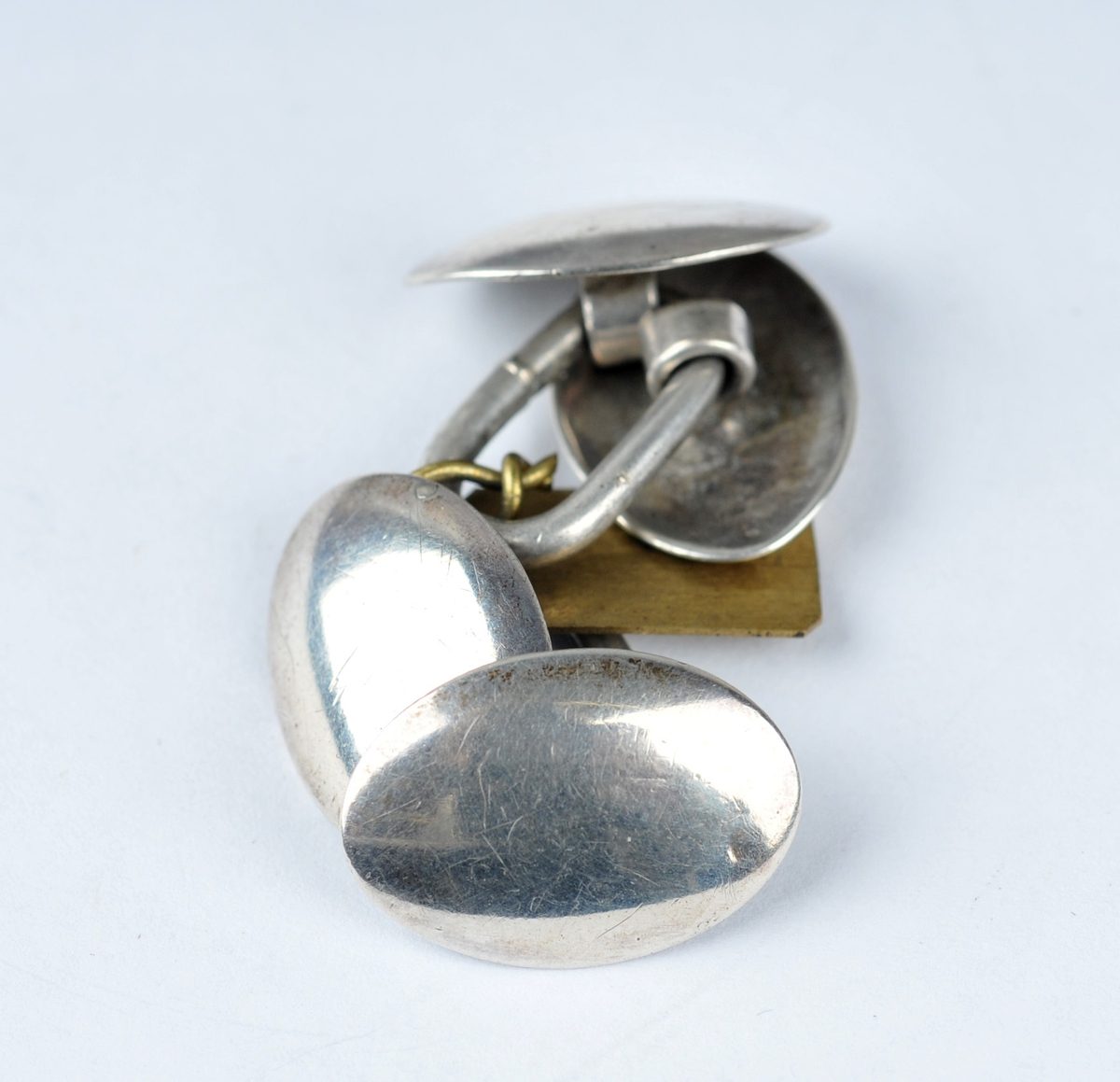Kvar mansjettknapp har to ovale, slette knappar bundne saman av lekkje.