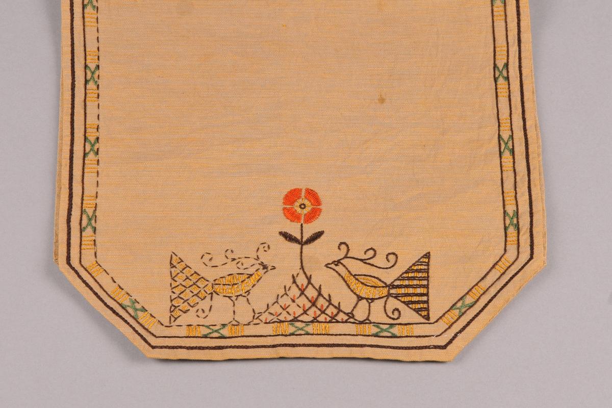 Løpar der hjørna er skrådde slik at løparen er åttekanta. Gul- og gråmelert botnstoff. Brodera med attersting, greinsting og sjattérsting med mouliénegarn i fargane brunt, grønt, orange og gult. Motiv ved kvar kortside: to påfuglar som står mot kvarandre med ein blom mellom seg. Smal bord rundt alle kantar.