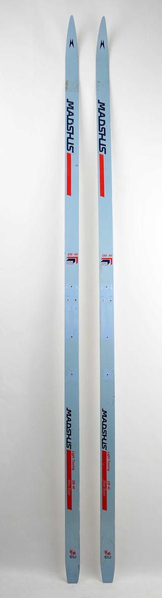 Langrennski laga av glasfiber. Metallic overside med raud og blå dekor/skrift. Kvit såle. Det har vore bora hol til bindingar.