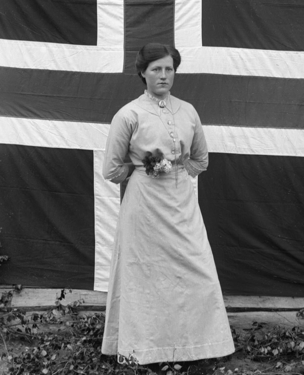 Kvinne i hvit kjole, foran norsk flagg