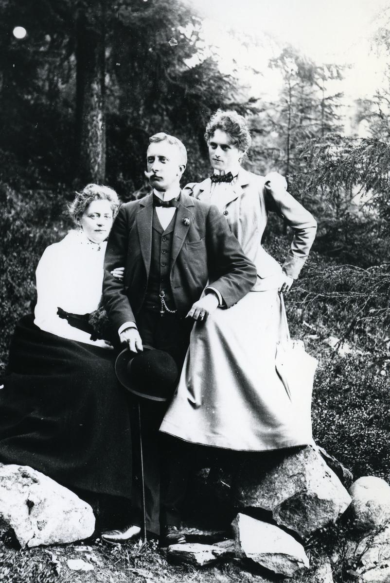 Mann og to kvinner, på steiner i skog