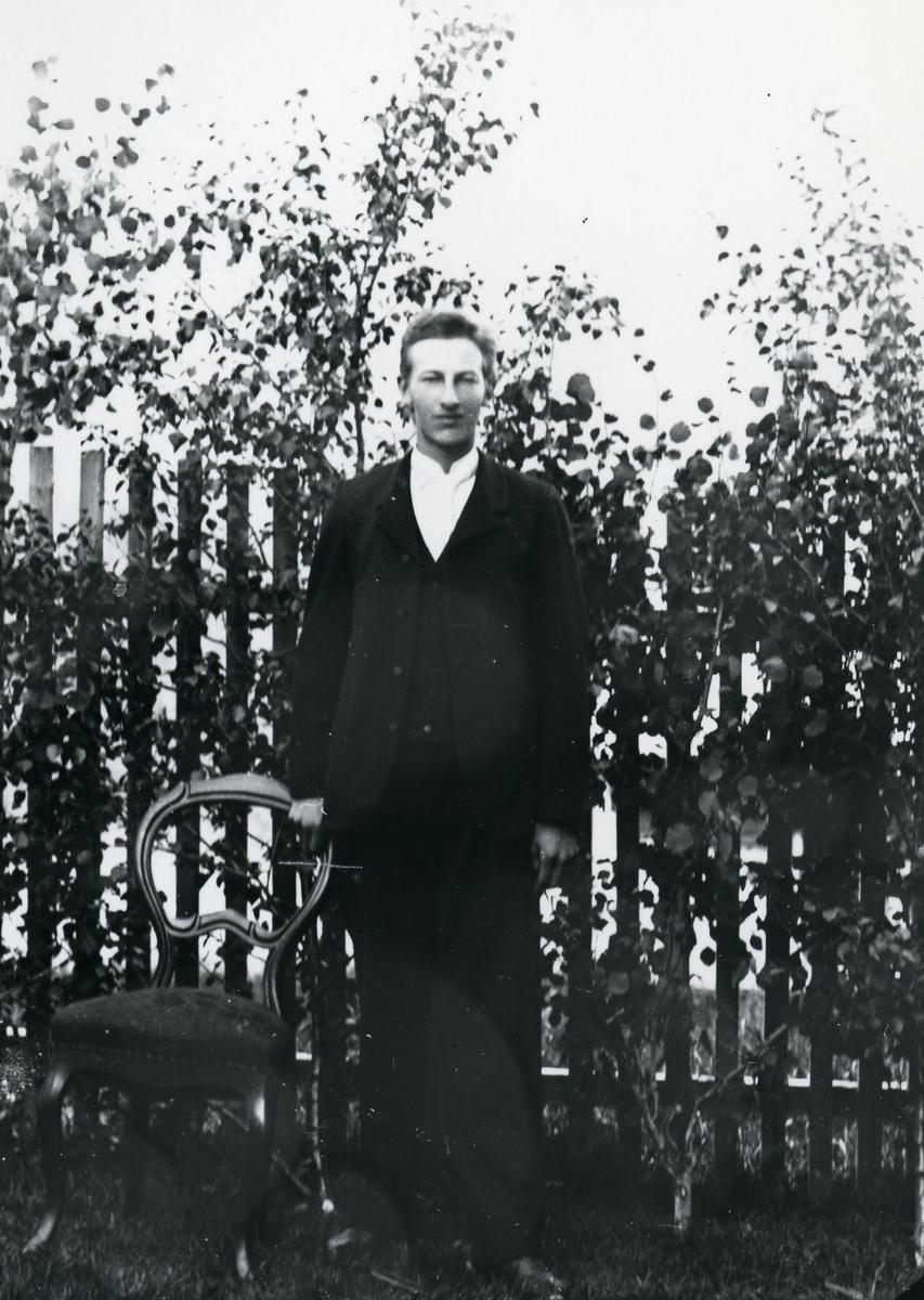 Mann i helfigur foran stakittgjerde og bjørkekvister, ved stol