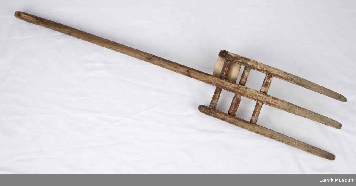 Form: 3 tenner hvorav den midterste er en fortsettelse av skaftet. 2 sidetenner festet ved 3 gjennomgårende tverrtrær. skaftet buet øverst.