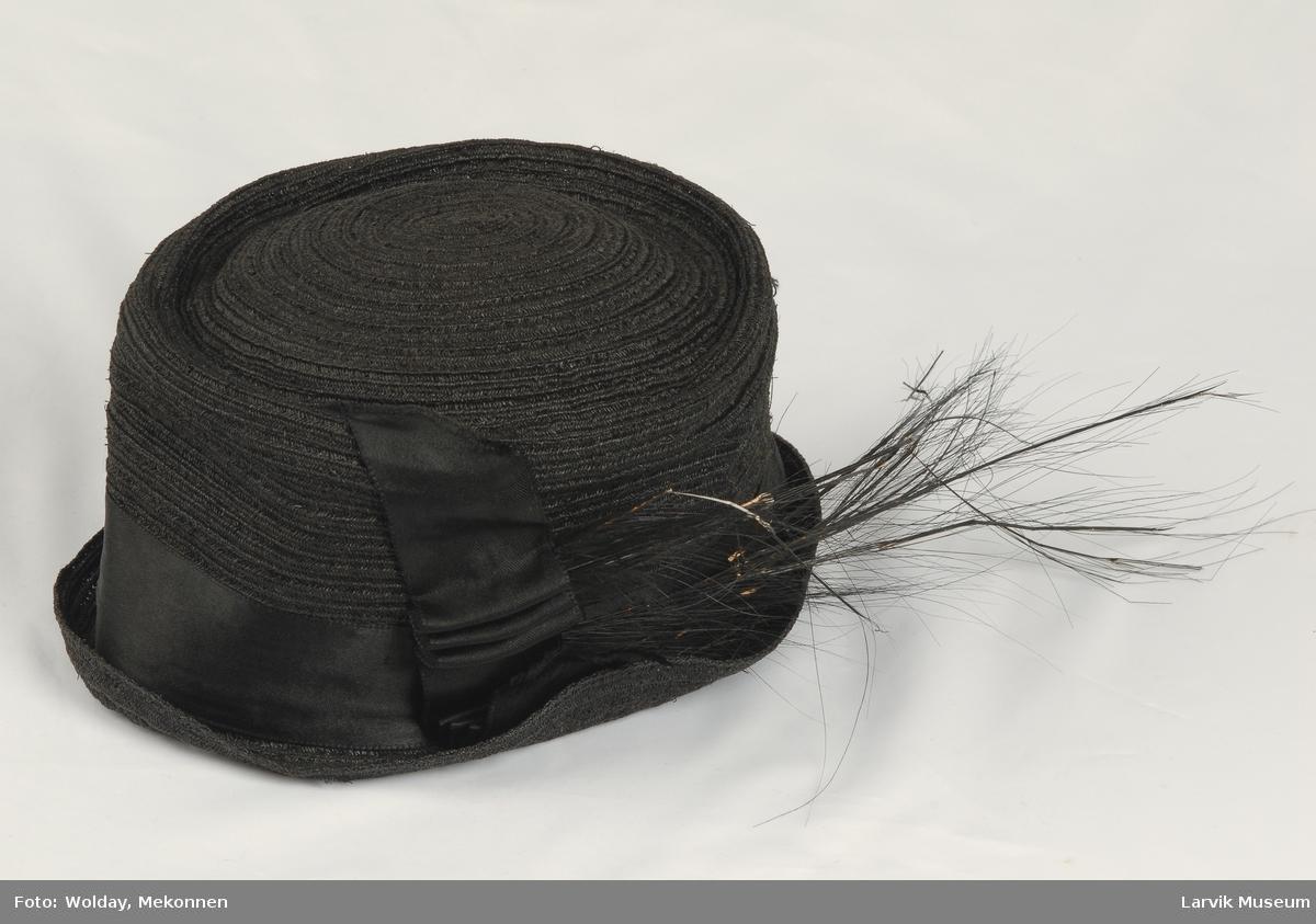 Form: Rund pull med silkebånd rundt, parti med drapert parti på siden. Pyntet med sort fjær.
