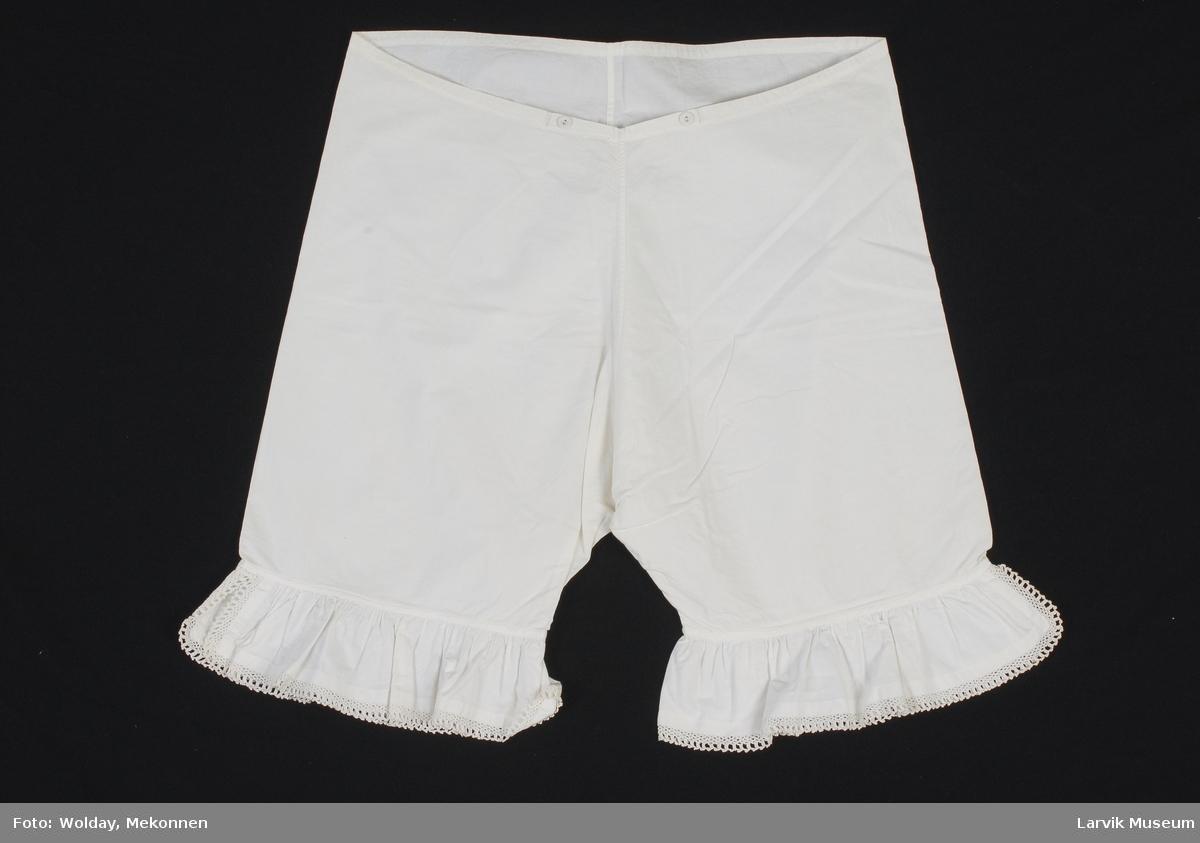 Form: Bukser til knærne, heklet blonde nederst, to lerrets knapper foran i livet for stramming.