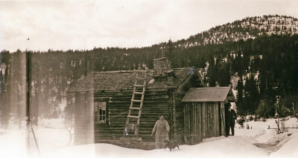 Stue av tømmer, kvinne, mann og hund på utsiden