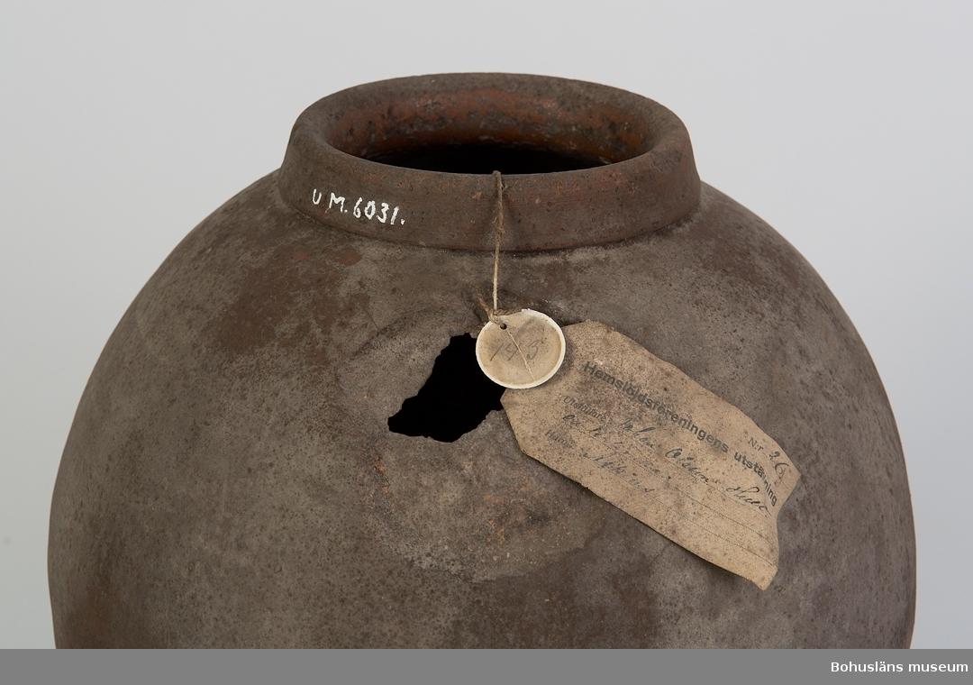 Ur handskrivna katalogen 1957-1958: Lerkrus (Hemslöjdsutst.) H.: 48 cm. Diamet.: c:a 12 cm. Glaserad. Med sex fötter. Ngt defekt. Mögligt.  Enligt etikett fastsatt runt mynningen: Hemslöjdsföreningens utställning [föremål] Nr 26 Utställare Johan Olsson Hult en lerkruka Härad Askims  På mindre rund etikett som troligen varit kantad med en metallring är skrivet: 143