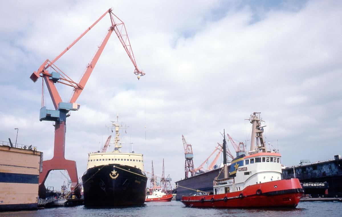 Fartyg: HELIOS                        Bredd över allt 9,48 meterLängd över allt 32,60 meterReg. Nr.: 7321659Byggår: 1973Varv: Åsiverken, ÅmålÖvrigt: Denna bild är tagen under en rundtur med någon av PADDAN-båtarna i Göteborgs hamn, ovisst exakt var: LENINGRAD, sovjetiskt fartyg t v som inte kunnat identifieras närmare (flera fartyg har burit detta namn) bogseras av bogseraren HELIOS, ex VICTORIA, senare ARCTIC HELIOS. Vem som ägde HELIOS vid fotograferingstillfället har inte gått att fastställa.