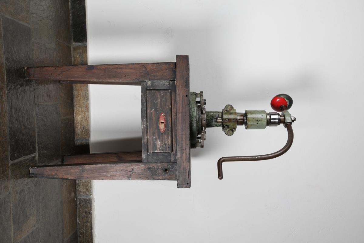 Maskin som brukes til å forme medaljer ved hjelp av slagkraft. Den har en sveiv som er festet øverst til en vertikal sylinder som har funksjonen å presse ut medaljenes form. Maskinen er montert på ett trebord som har en skuff og fire bein.