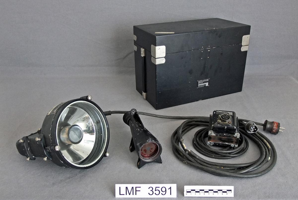 Signallampe / morselampe med tilhørende, låsbar kasse. Denne signallampa har vært benyttet i åpen sjø  (til havs) for å signalisere mellom skip  v.h.a. morse-koder.  Form:  lampefronten sirkulær, transformatoren samt kassa rektangulær.