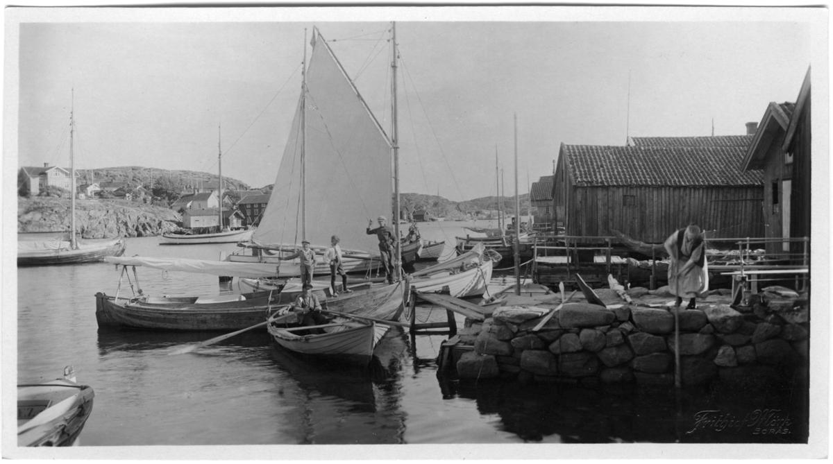 'Kilen åt S. I förgrunden båtar . I en båt står 3 unga män och i 1 eka sitter 1 äldre man. 1 person på bryggan. Hus. ::  :: Serie fotonr 1888-1963.'