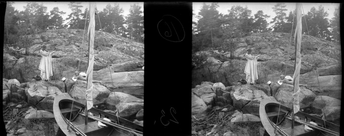 'Bildtext: ''Rhoda soltorkar.'' :: Vy med 1 kvinna som stående på berghäll (Elsa) och 1 flicka, Rhoda, som ligger och solar på berghäll. I förgrunden en båt med ihoptaget segel. ::  :: Ingår i serie med fotonr. 5259:1-16. Se även hela serien med fotonr. 5237-5267.'