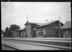 'Vy med järnvägsspår i förgrunden och troligen tågstationshu