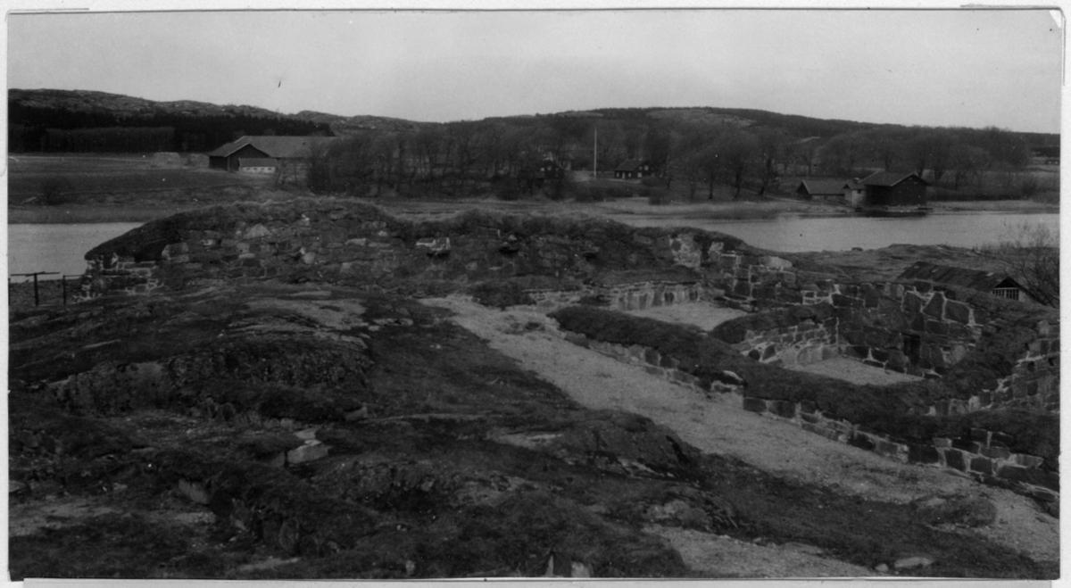 'Bildtext: ''Platsen för Konghelle (Kastellgården i Ytterby socken) sedd från Ragnhildsholmens fästningsruin.'' Vy över ruin med stenmurar. I bakgrunden gårdsbyggnader. ::  :: Fotonr. 7048:42-46 indelad under rubriken ''Skogens historia i Göteborgs och Bohus län under historisk tid''. Ingår i serie med fotonr. 7046:1-383, 7047:1-33 och 7048:1-67 med bilder från  Länsjägmästare John Lindners bildarkiv.'