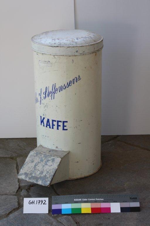 Form: Falsede kanter. Lokket på toppen av beholderen har buet overside. Skuff til uthenting av kaffe har skrått lokk som er hengslet. Beholderen er malt i grått med blå bokstaver: CHR.J. STEFFENSENS KAFFE