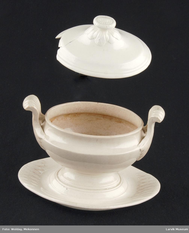 Form: ovalformet kopp med fast skål og to høye hanker lokket har åpning for øse. utpresset dekor på skål, håndtak og lokk. håndtakene gjennombrutt.