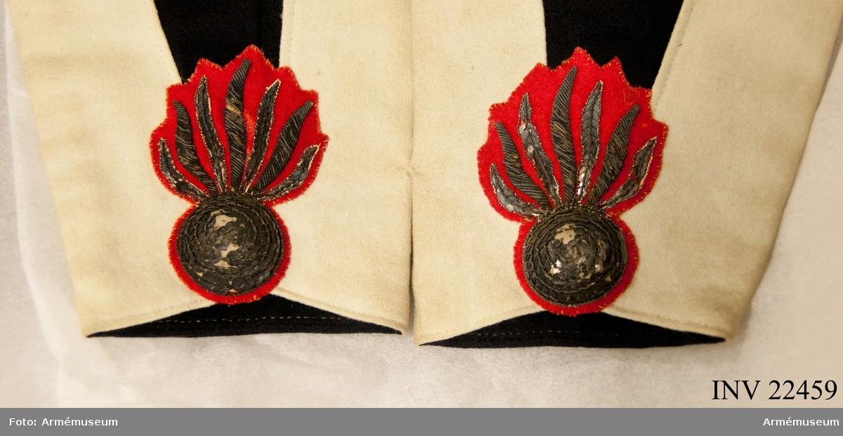Grupp C I. Ett par granater broderade i paljetter och guldkantilj på rött kläde. På frack enl. Svenska arméns rulla 1835.