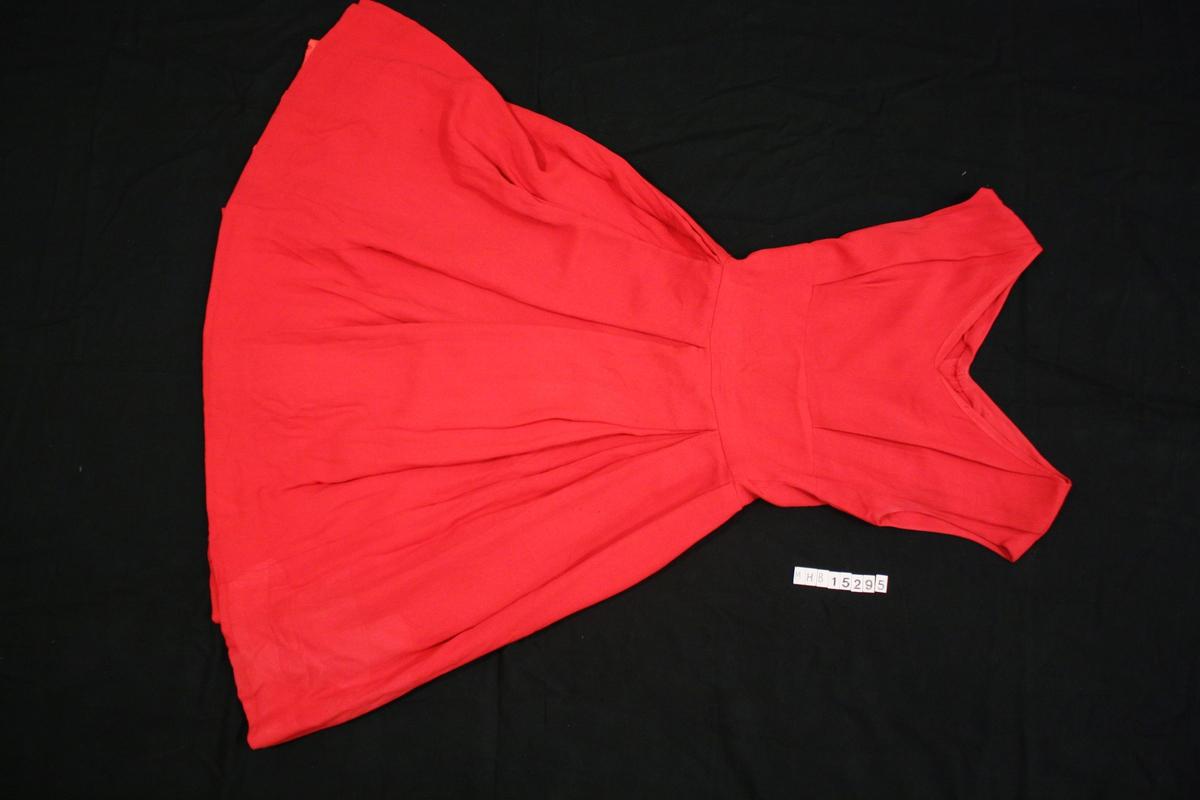 V-skåret hals uten ermer, innfelt midstykke, skjørtet er foldet. Glatt rødt fór i skjørtet. Glidlås på bakstykket.