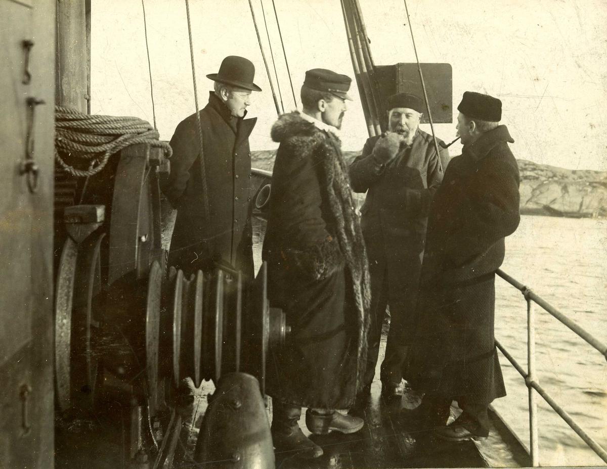 Gruppebilde av fire menn som står på dekk på et fartøy.