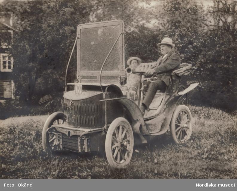 """General Motors. """"Baksidestext i svag blyerts: Grosshanl. Evald Lönnberg sommaren 1909 i hans första automobil """"Maurer Union"""", 5 hkr. Ludwig Maurer i Nürnberg bedrev automobiltillverkning före första världskriget. Ett fordon väldigt likt detta finns i Schlumpfsamlingen i Mulhouse i Frankrike. Den är daterad 1901, så bilen på bilden var troligen ett antal år gammal 1909. Den hade kraftöverföring via friktionsskiva. Registreringsnumret D2 antyder att platsen är någonstans i Södermanland."""""""
