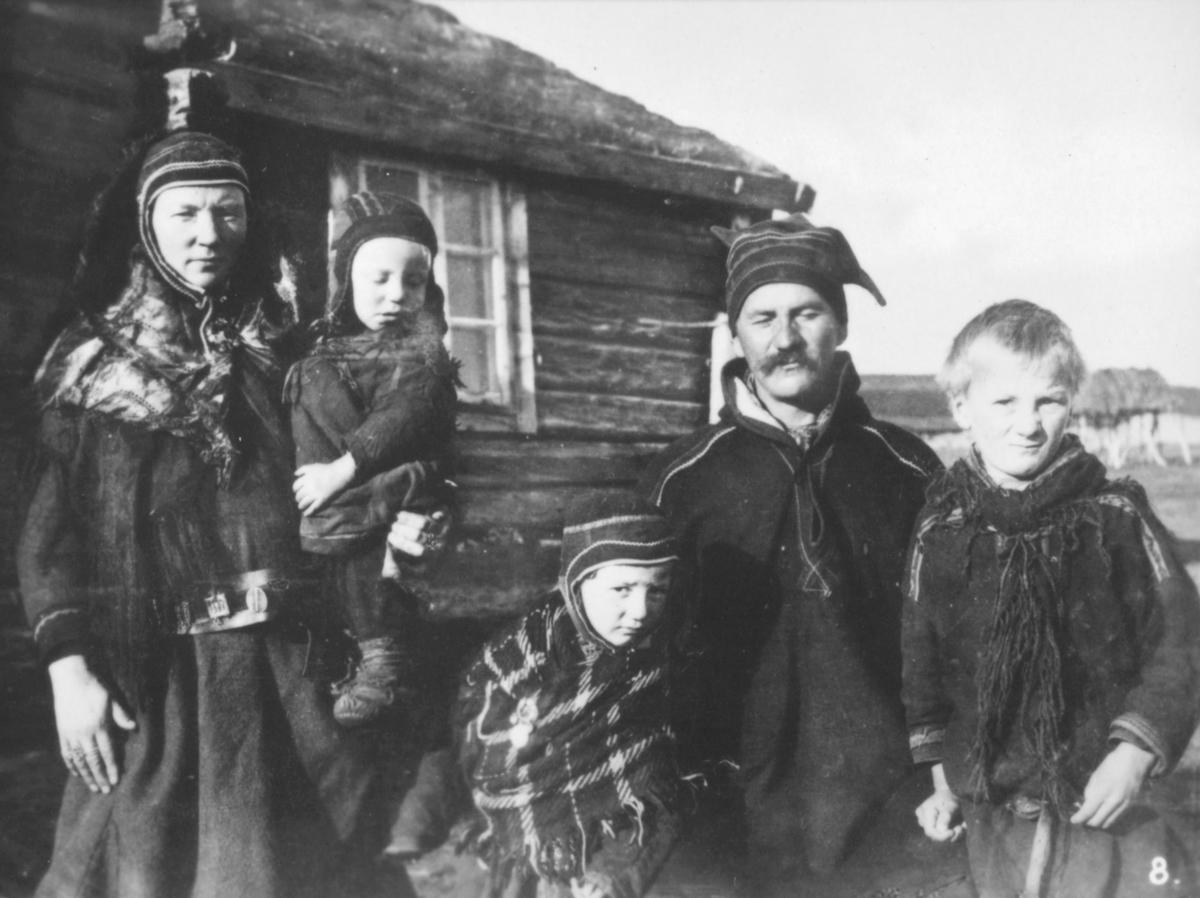 Bilde nr. 8 i serien '10 amatørbilleder fra lappernes hjem og liv i Finnmark', se FB 93164-001. 'Britamatti med familie, Kautokeino.' Britamatti med kone og tre barn, fotografert uten for et hus. De er kledt i samekofter, luer og skjerf.
