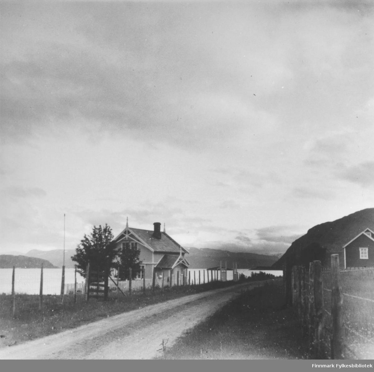Landskap med grusveg og noen hus.
