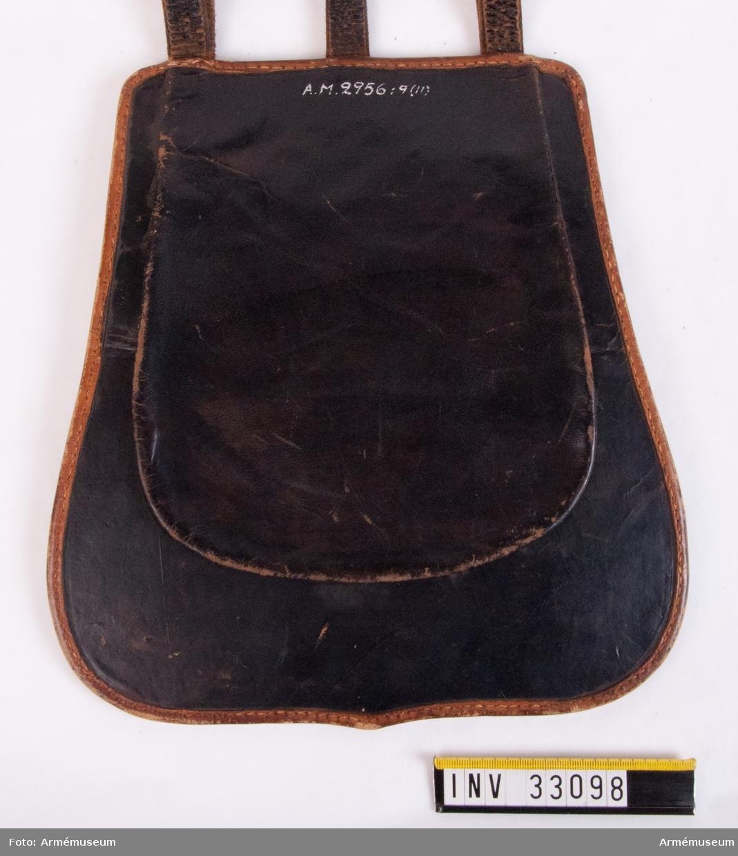 Grupp C I. Ur uniform för manskap vid Kronprinsens husarregemente. Livplagg m/1845. Bestående av dolma, päls, byxor, mössa, skärp, kartusch, rem t kartusch, handrem, stövlar, sporrar, taska, remmar, koppel, halsduk. Taska enligt go 28/6 1825; dock ej närmare beskriven.   Taska av läder med lock av gul och blå vadmal och läderskodd kant. Lockets gula framsidan har en blå sköld med tre gula öppna kronor under en sluten gul krona. Skölden omges av en gul snodd.
