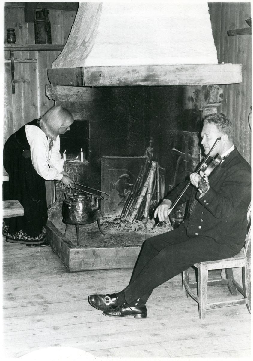 Torleiv Bolstad sitter på en stol og spiller fele, mens Oddrun Rudi står ved siden av og fyrer i en åpen grue.