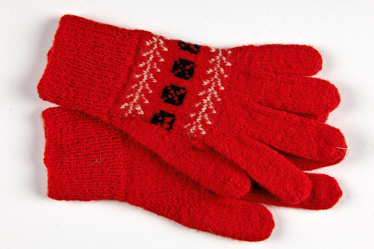 Fingervante i 2-trådigt rött ullgarn. 5 cm resår slätstickad med mönster Rutan i mörkblått och naturvitt på röd botten. Den mönsterstickade delen är ihopsydd med vanten på två sidor.