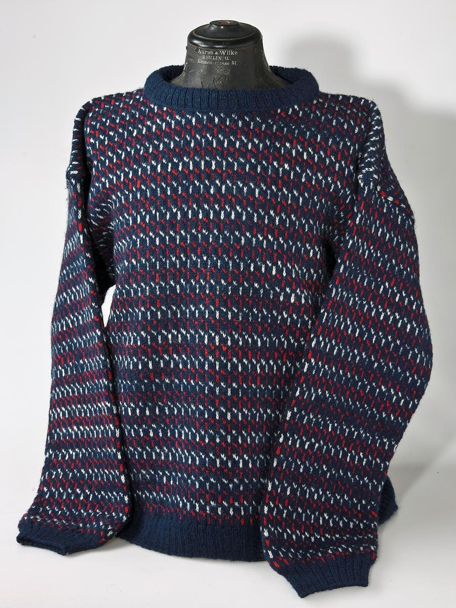 Bingestickad tröja i 2-trådigtullgarn.  Rött och vitt mönster på blå botten.  Resårstickad nederkant, ärmmuddar och halskant