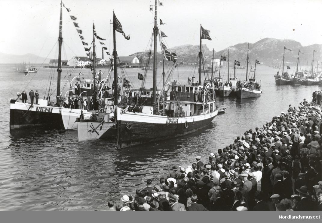 """Bodø havn. Stor folkemengde på kaia. Flere skøyter med signalflaggene heist. Burøya i bakgrunnen. I fgr. N 31 ME (Meløy) Mk """"Bølgen"""""""