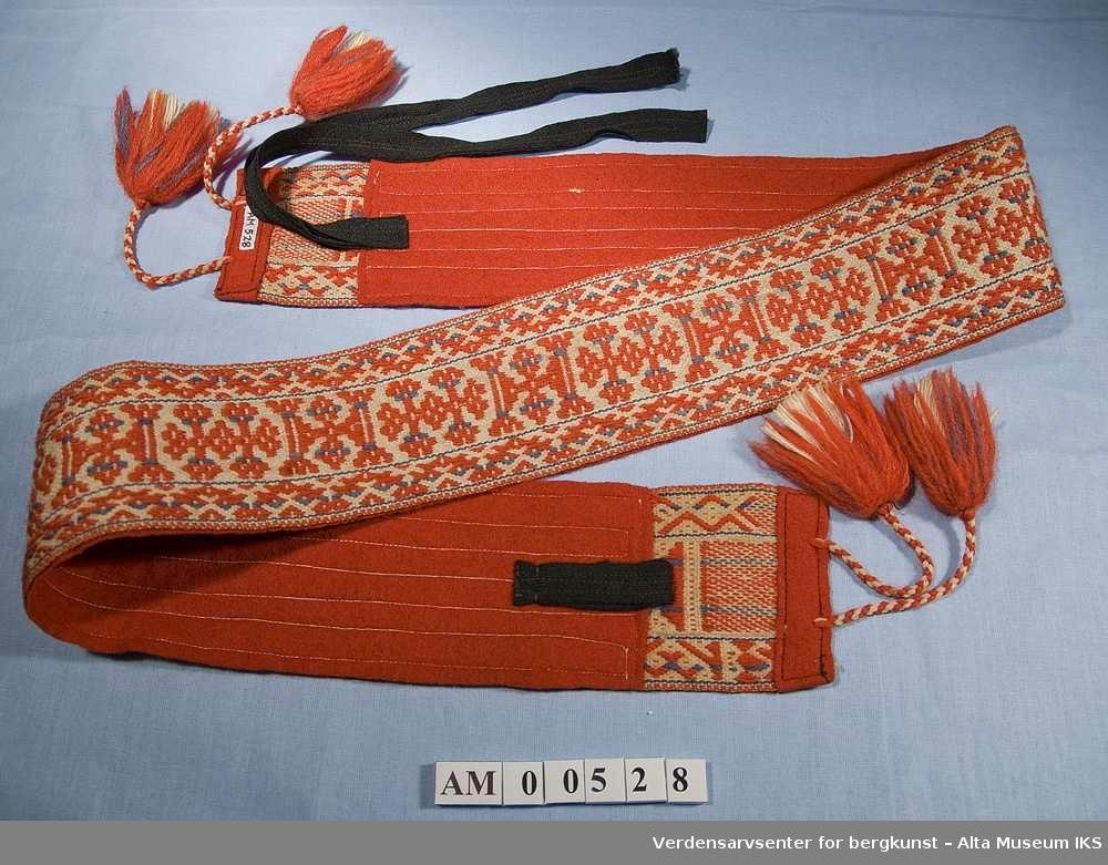 Grindveved belte med beltekant. Foret og kantet i endene med rødt klede. Lukkes med to stoffremser i ene enden og hempe i andre som er sydde i svart bomullstoff. I begge endene av beltet er det påsatt to flettede snaorer med dusker som pynt. Snorenes lengde 15 cm.
