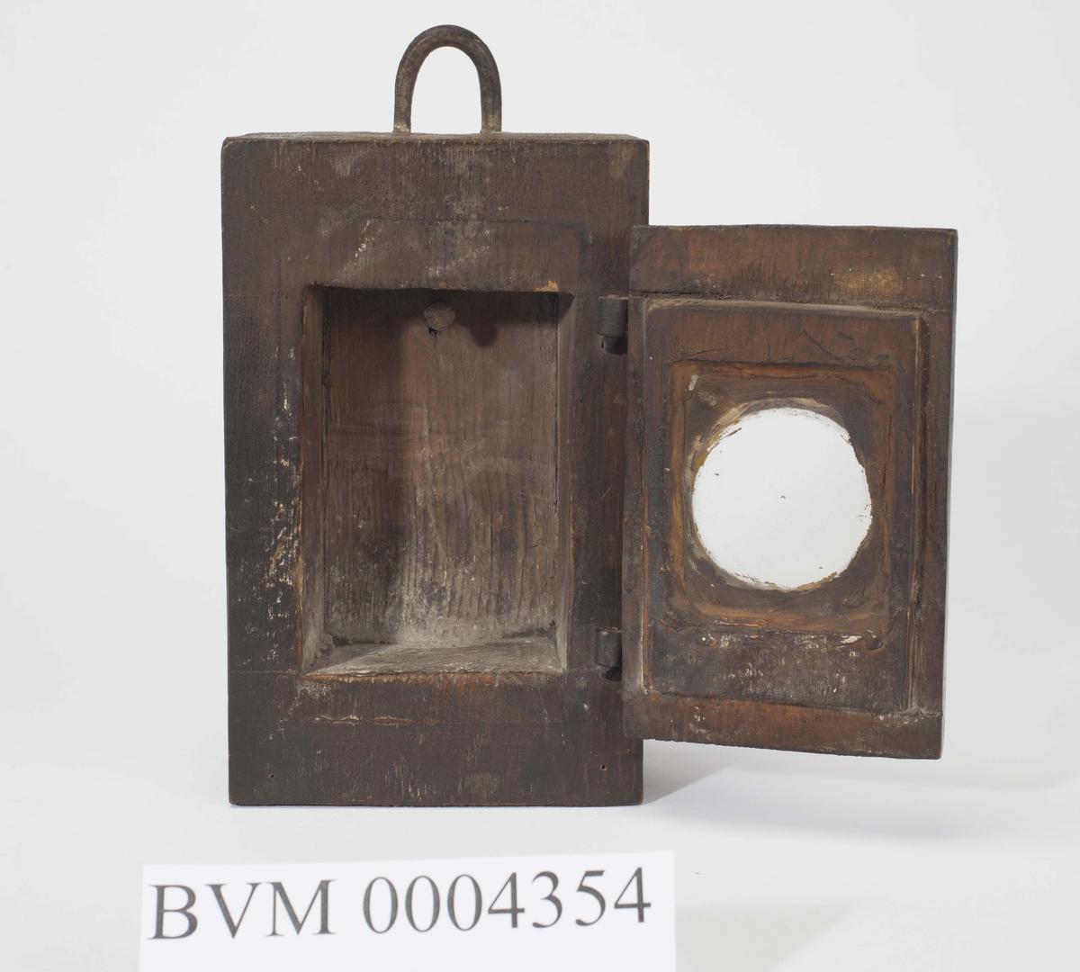 Kasse for oppbevaring av oppholdsuret. Grovt uthula trekloss med ei dør med glass i. Her hang uret.