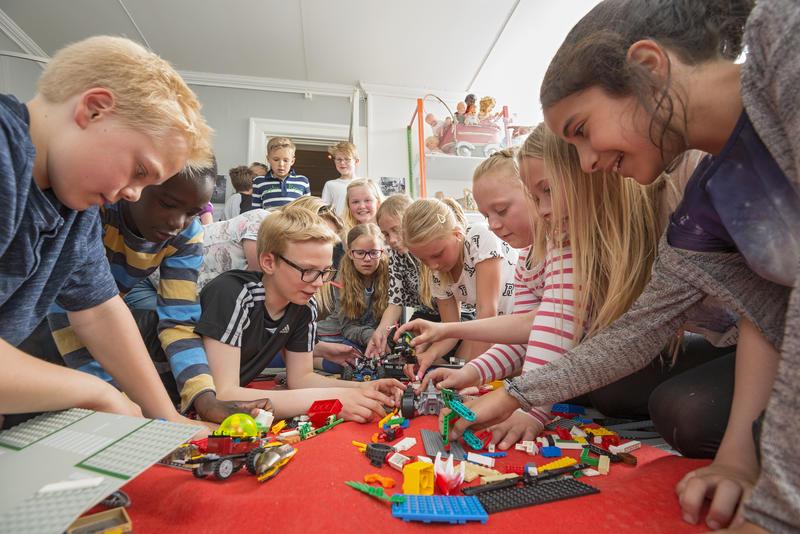Skoleklasse leker med lego i leketøysutstilling. Foto/Photo