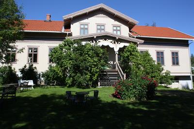 Kvinnemuseet med blomsterbed og sveitserstilveranda