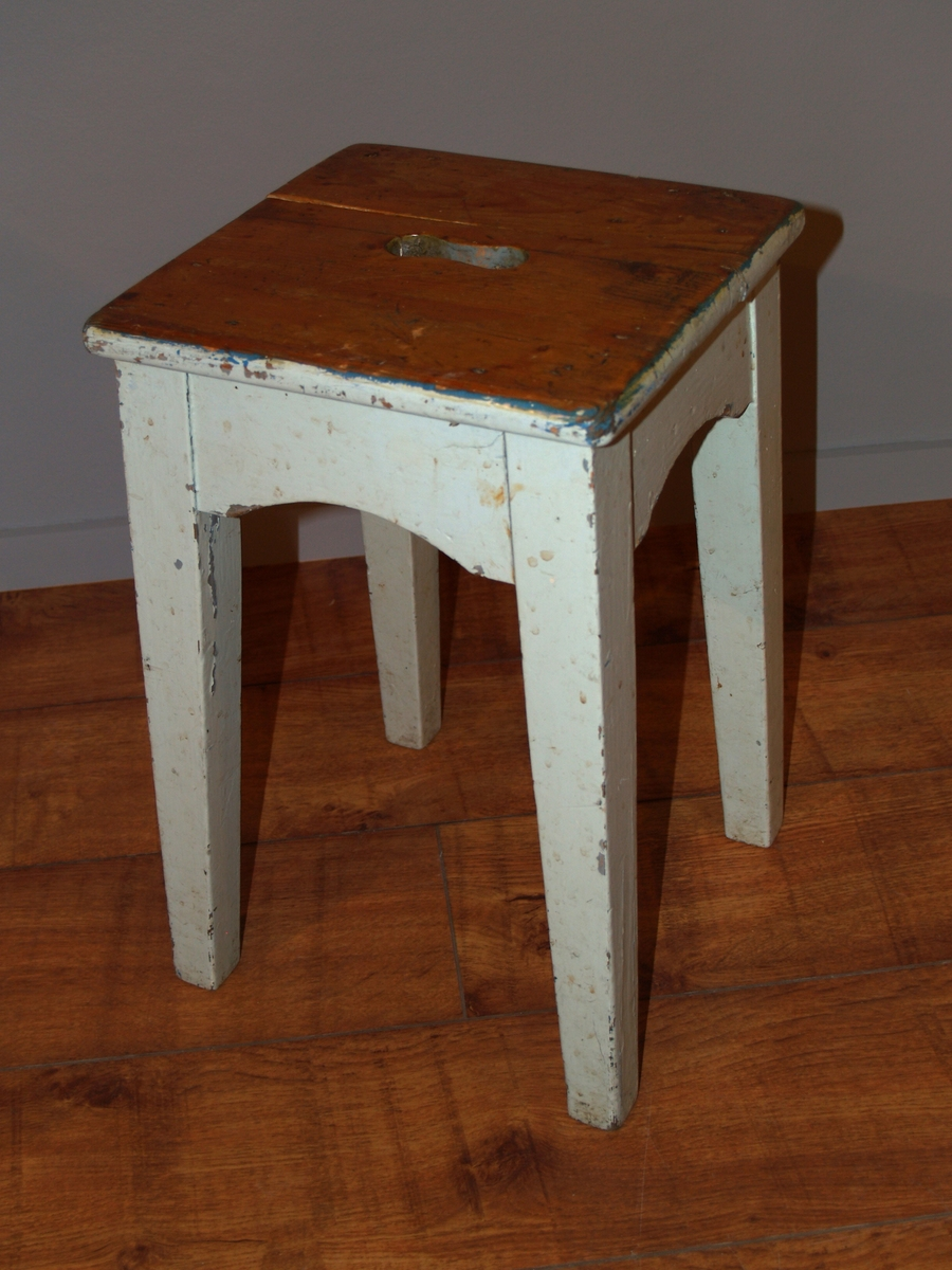 Kvadratisk sitteplate med ovalt gripehull. Fire bein.