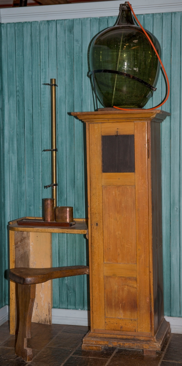 Skap med tre hyller og dør. På siden er det festet et bord. På toppen av skapet er det montert en rund beholder og på bordet er det montert ett analyseapparat.