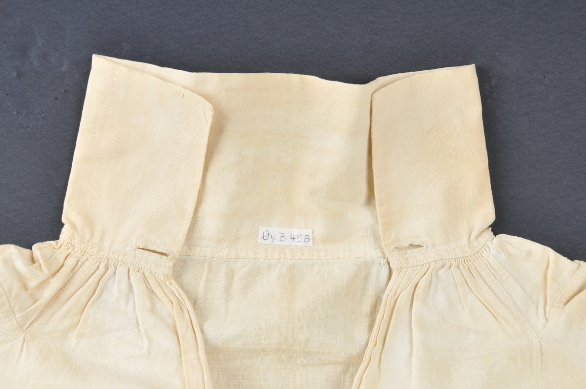 Herreskjorte med splitt midt framme. Det er spor etter fylling/forsterking nederst i splitten. Skjorta har høg halslinning, skulderklutar, lask under armane og isydd ein dobbeltlagt trekanta kile nederst ved sidesaumane (dialekt: steglapp). Armane er skøyta saman på langs av to stoffbredder. Handsydd med lintråd med attersting, smale indresaumar. To knapphol i begge endar av halslinningen og to knapphol i kvar armlinning. Jarekantar i høgre sidesaum. Ein synleg rynketråd både ved hals- og armlinningar.