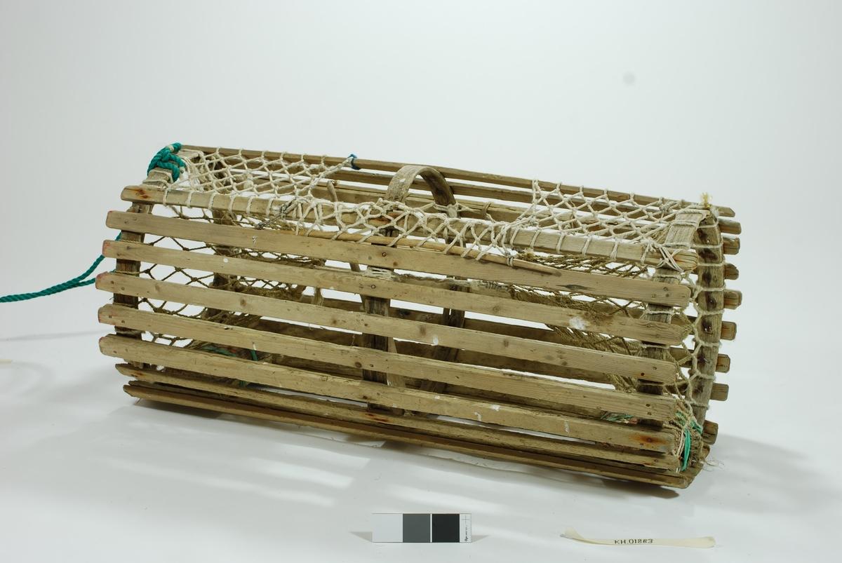 """Sylindrisk lektetene med to motstående kalver i kortsidene. Ringene er av glattskurte energrener. Agnspyd i tre.   Garnet er hjemmespunnet hvalfangertrosse av grov dimensjon. Lukkeåpning av gammel type med tverrpinne (håndskåret ekepinne). Noen reparasjoner av nyere dato.  bl.a. grønt nylontau for ekstra forsterkelse av nederste rekke av vannrette sprøtt. Synkesten i granitt festet med grønt nylontau. Intet spor etter barking/tjære.  Moderne tauverk med plastblåser og nylontau av ulik kvalitet. Væler, 3 stk: trevæle, glasskule og gummikule. Trevæle er hvit  m/blå striper. T.P. skåret inn. Mål: 42,5x8. Oransje gummikule (plastvæle). Merket Ø-27-H og 11 på toppen. Stemplet Made in Norway / 20"""" / Scanmarin Aandalsnes. Omkrets 48 cm. Glassvæle: Omkrets 45,5 cm"""