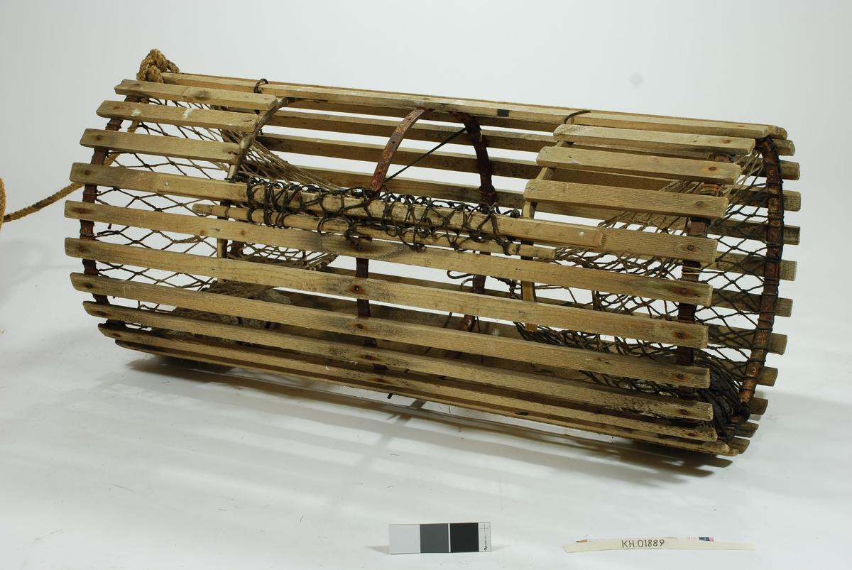 Rund/ sylindrisk sprøtt-tene. Hjemmespunnet garn med store masker. To motstående innganger i kortsidene. Intet fangstkammer. Kalveringer i metall, ovale i formen tilpasset krabbens fasong. Ovalformet åpning i toppen forsterket med ubehandlede barkkledde enerkvister som er formet til. Metallgjorder virker solide og kan være spesiallaget. Agnspyd i metall horisontalt plassert med ekstra sperre i kalveringen. Synkestener i granitt i hver ende, bundet fast med sort tauverk. Åpning med gammeldags lukkepatent med garn og håndspikket pinne. Tena bærer preg av tidligere å ha vært tjæret/ barket.   Store mengder gresstau og fem væler, tre stk. i treverk og to stk. av kork.  Hvitmalte trevæler i tre størrelser: Størst: 63x9 cm. Mellomst: 51x9 cm.  Minst: 41x9 cm. Alle har profilerte kanter og er hvitmalte med sort ende (tjæret). Malingen er nesten slitt av. K.V er skåret inn i de tre fløtene. Korkvæler: Lengde: 22cm Omkrets 32 cm. K.V risset inn i den ene.