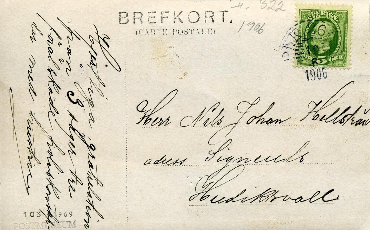 Brevkort med fotografiskt motiv: en herre som håller ett brev och en dam stående bredvid med ett ljus, båda läser brevet. Tre uniformsklädda herrar försöker nyfiket se vad som kan stå i brevet.