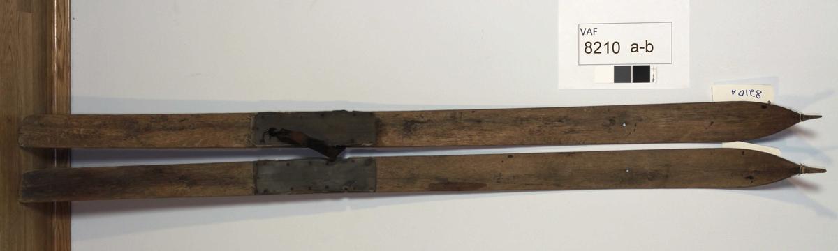 Form: Avsmalnende/jevnbred. Rygg: Svak bue, flat underside, rett avskåret bak. Binding: tårem av lær (med knyting) på en ski. Fotplate: Antagelig flere lag gummibelegg.