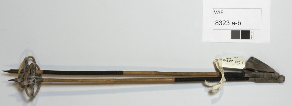 Skistaver, slalomstaver. Stenger (bambus) m/håndfeste m/lærløkke ene ende, metallspiss og ring (bambus) i lærfeste (i kryss) andre ende.
