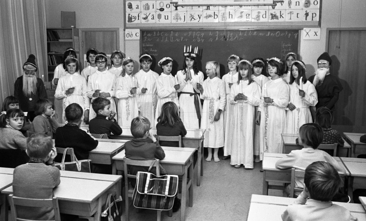 Lucia, Trafikolycka, Sörbyvägen Lillån 13 december 1966Ett Luciatåg bestående av barn i tioåårsåldern står uppställt i ett klassrum i en skola. En Lucia befinner sig i mitten klädd i vitt linne, rött skärp om livet och ljuskrona med glitter på huvudet. Tärnorna som står runtomkring bär också vita linnen med glitter runt liven. De bär ljus i sina händer.Två tomtar står på ömse sidor om tärnorna. Framför Luciatåget sitter en publik i form av en skolklass.
